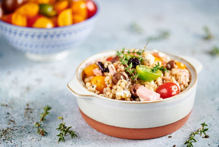 Barley salad with feta cheese, ham and olives