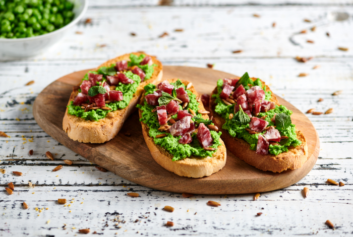 Toasted bread with peas cream, sunflower seeds and salame